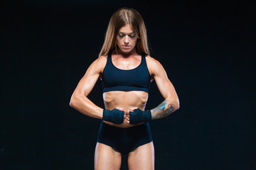 Black boxing bandages on the hands of a muscular girl in black clothes. Boxing, kickboxing, karate. Fitness, healthy lifestyle concept. Isolated on the black background. © satyrenko
