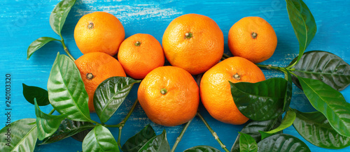 Banner Ripe tangerines with green leaves on a bright blue background Top view flat lay copy space - 240103320