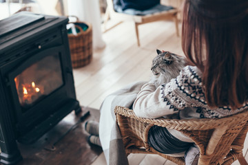 Human with cat relaxing by the fire place