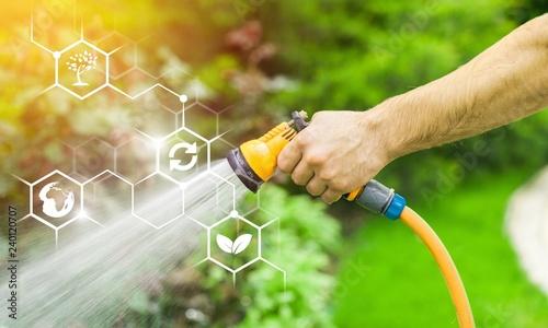 obraz lub plakat Watering green garden with outdoor hose