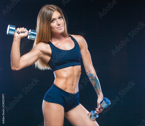 Muscular and sexy girl with long hair in black clothes with dumbbells of steel color. Fitness, healthy lifestyle concept. Isolated on the black background.