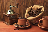 Coffee still life. A cup of coffee, a coffee grinder, a bag of coffee beans