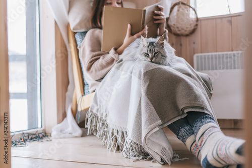 Girl relaxing with cat in cabin - 240143371