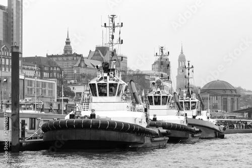 obraz PCV drei Schlepper an den Landungsbrücken in Hamburg in schwarz-weiß