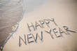 Happy New Year message handwritten in smooth, clean sand with a fresh wave coming up the beach
