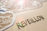 Reveillon, a French word used for Brazilian New Year's Eve celebrations, handwritten on smooth sand on Copacabana Beach in Rio de Janeiro, Brazil