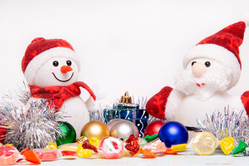 Beautiful Christmas and New Year composition with Santa Claus and snowman in red hats and scarves in front colored toys, candys and sweets