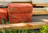 Building material for repairs in the garden-new red bricks, boards, lie on the grass