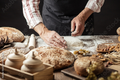 Hands of male chef cook working with dough, surrounded by bread and long loafs from whole wheat flour. Bakery concept. Homemade bakery concept - 240231560