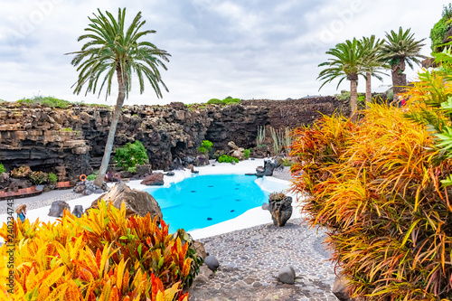 Leinwanddruck Bild Beatiful exterior of the Jameos del Agua with pool and colorful trees, Lanzarote, Canary Islands, Spain