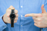 Time management concept. A man in a blue shirt holds a black watch and points his finger at them.