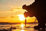 The angler fisherman at ice winter fishing. Sunset - 240348324