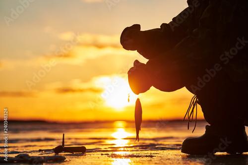 obraz lub plakat The angler fisherman at ice winter fishing. Sunset