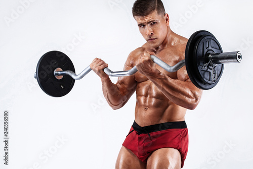 Brutal strong muscular bodybuilder athletic man pumping up muscles with barbell on white background. Workout bodybuilding concept. - 240356500