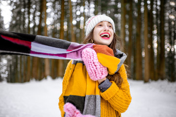 Portrait of a young playful woman dressed in bright winter clothes standing in pine forest enjoying winter time