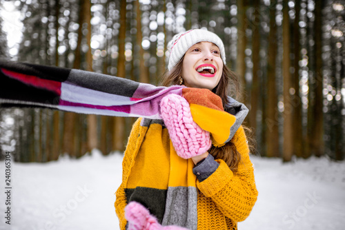 Portrait of a young playful woman dressed in bright winter clothes standing in pine forest enjoying winter time - 240365304
