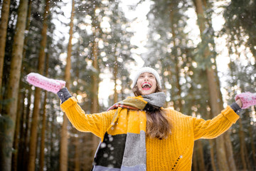 Portrait of a young exccited woman dressed in bright winter clothes enjoying snow falling in pine forest © rh2010