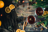 two glasses with mulled wine on the table with orange slices and spices - 240365799