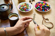 Close-up of woman sitting at the table drinking coffee and making handmade accessories from colorful beads