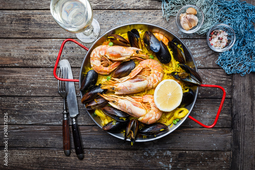 Traditional spanish seafood paella in a fry pan on a wooden old table, top view - 240376126