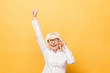 Portrait of a cheerful senior woman gesturing victory isolated over yellow background. Using phone.