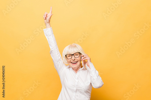 Foto Murales Portrait of a cheerful senior woman gesturing victory isolated over yellow background. Using phone.