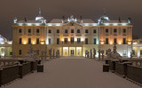Branicki Palace in Bialystok at night in winter scenery. Snow-covered garden and walls of the palace highlighted with stylish lamps.