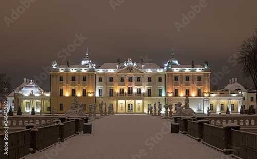 Branicki Palace in Białystok in Poland at night in winter scenery. Snow-covered garden and walls of the palace highlighted with stylish lamps.