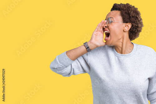 Leinwanddruck Bild Young beautiful african american woman wearing glasses over isolated background shouting and screaming loud to side with hand on mouth. Communication concept.