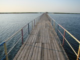 Panorama of a long wooden bridge across the bay leading to the beach on a small island.