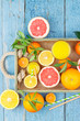 Set of different fruits and glass with fresh orange juice, wooden tray