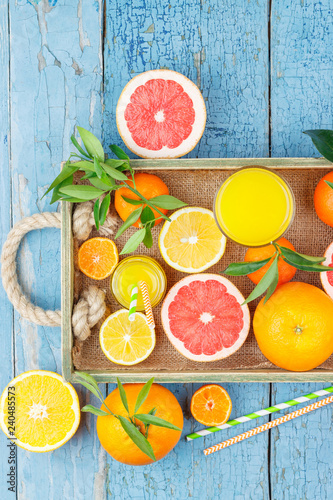 Set of different fruits and glass with fresh orange juice, wooden tray - 240485573
