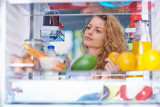 Woman standing in front of fridge full of groceries and looking something to eat. Picture taken from the inside of fridge. - 240485928