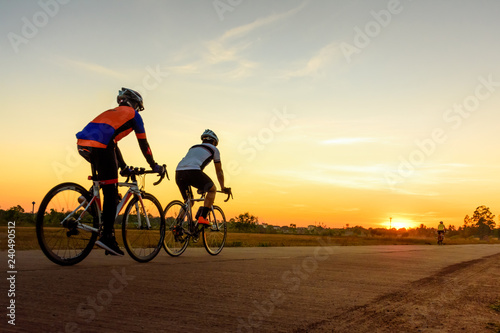 Men ride bicycles on the road with beautiful colorful sunset sky. Sport and active life concept.