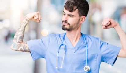 Young handsome nurse man wearing surgeon uniform over isolated background showing arms muscles smiling proud. Fitness concept.