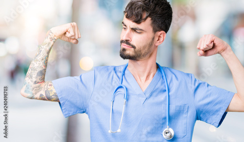 Leinwanddruck Bild Young handsome nurse man wearing surgeon uniform over isolated background showing arms muscles smiling proud. Fitness concept.