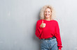 Leinwandbild Motiv Young blonde woman with curly hair over grunge grey background doing happy thumbs up gesture with hand. Approving expression looking at the camera with showing success.