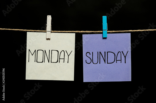 Copy space. Monday and sunday. Two colored sheets with the names of the days of the week. Stickers attached to a clothespin.