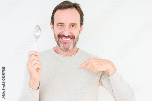 Leinwanddruck Bild Senior man holding silver spoon over isolated background with surprise face pointing finger to himself