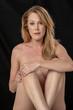 Emotional Nude Figure Model Posing Against A Black Background