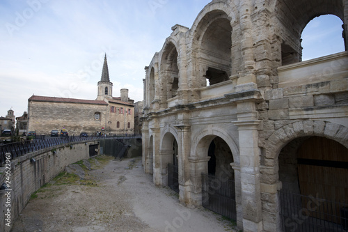 Arles, France - April 29 / 2018 : Arles Amphitheatre at the right side and the church at front