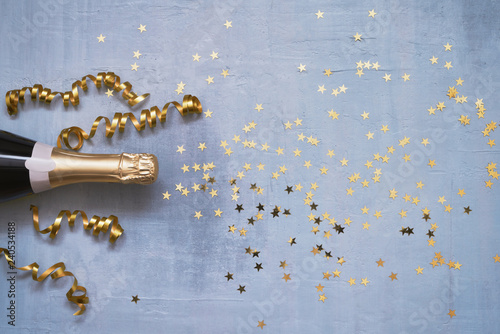 Champagne bottle with confetti stars and party streamers on blue background. Copy space,top view. Flat lay - 240534188
