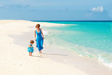 Mother with her Cute baby in blue dress walking on the white sand beach on the shore of the turquoise ocean. Boracay. Philippines. Family vacation