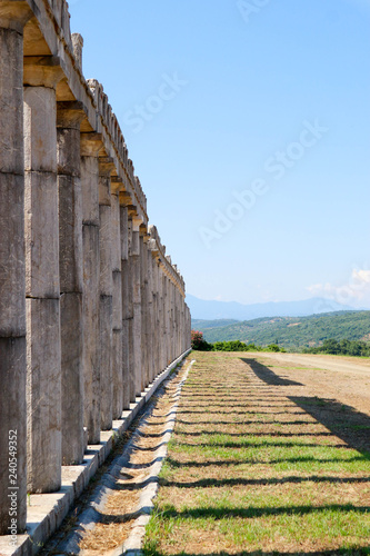 Сolonnade of stadium, row of columns, in ancient Messini, Greece, in sunny day