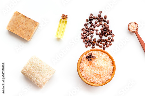 Aromatherapy and spa concept. Spa salt with coffee scent near soap, spa oil and loofah on white background top view