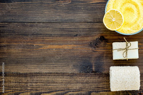Lemon spa salt and spa assessories like soap, loofah, spa oil on dark wooden background top view copy space