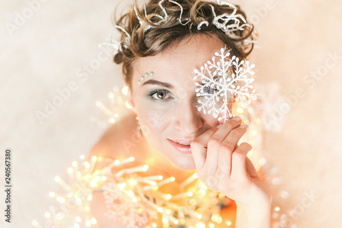 Christmas wishes. Happy New year photography. Photo with lights. Smiling woman with warm garland and glitter snowflakes in close up portrait.