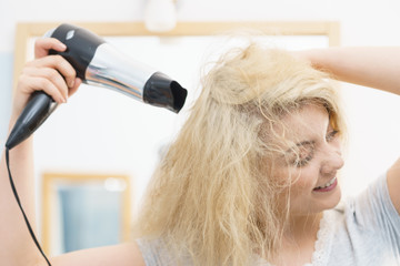 Blonde woman using hair dryer © anetlanda