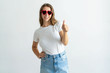 Woman wearing heart shaped sunglasses and showing thumb up. Smiling pretty young lady looking at camera. Recommendation concept. Isolated front view on white background.