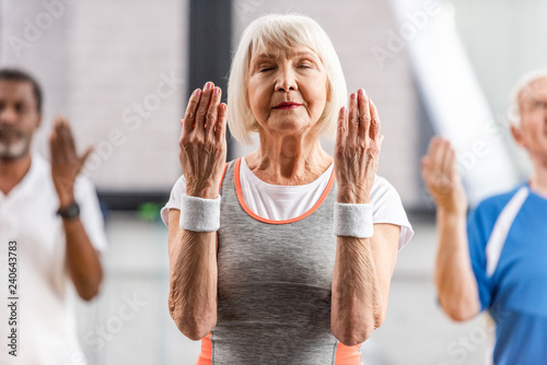 Poster selective focus of senior sportswoman with closed eyes making exercise at gym